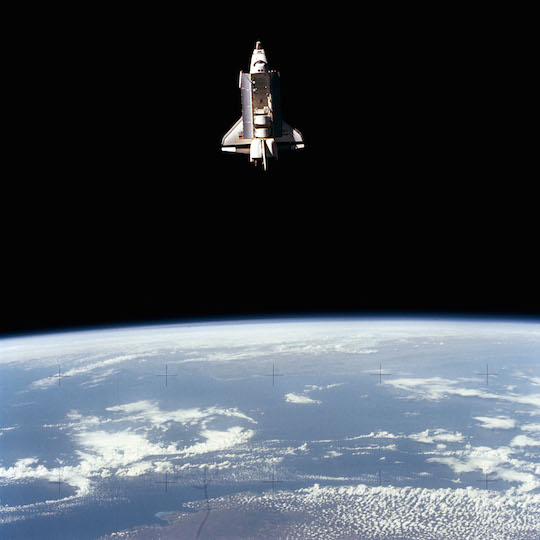 Photo of Space Shuttle Challenger in orbit above the earth